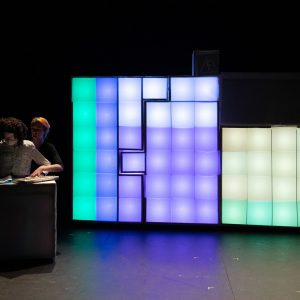 A large tetris like set is lit up on a black stage. The set blocks are divided into smaller squares, each with their own light and they are displaying different colours. The boxes are lit up in sections of green, purple, yellow and red and it is reminiscent of the periodic table. In the shadows to one side is Kate, a female human size puppet and her puppeteers.