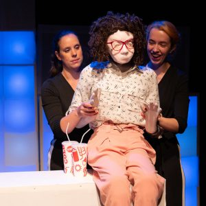 Kate, a female human sized puppet with red 80s glasses and a tight perm, is sitting on a tall white box, her feet are not in shot. There are 2 cups of soft drink with straws next to her. She is raising her hands and looking forwards. Also visible are 2 puppeteers wearing black, one on either side of Kate. The one on the right is laughing.