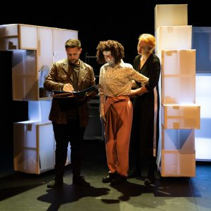 Kate is standing on stage next to Dr Bagshott, as they look at an a4 binder folder. There is a puppeteer in black standing behind Kate and looking over her shoulder. Kate is a female human sized puppet with red 80s glasses and a tight perm, she is wearing pink trousers and a white speckled shirt. Dr Bagshott is a white male with short dark hair and short facial hair, he is wearing an old brown leather jacket.