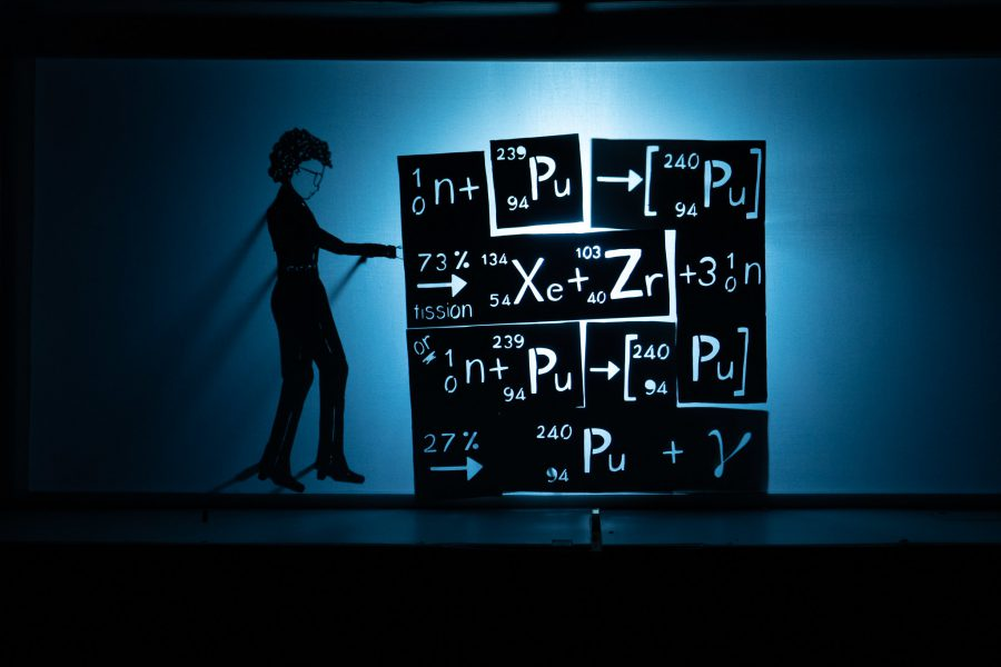 This is a silhouette, shadow puppet image, it is black and white with hints of blue in the shadows. A shadow puppet figure of a woman is standing next to a large block of tetris like shapes piled together, the shapes show chemical symbols and equations including plutonium, Xenon and Zirconium.