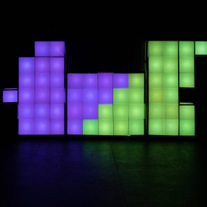 3 large tetris like set blocks are lined up next to each other on an empty black stage. They are lit up in bright green and purple lights, split with a zig zag line across the central rectangular block. The blocks on the left and right have uneven edges but all are made up of smaller squares which line up like in tetris when put together.