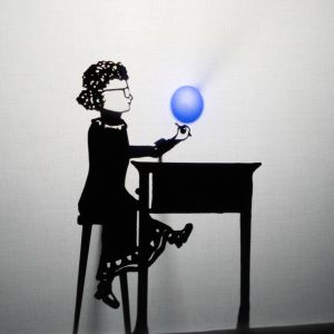 This is a silhouette, shadow puppet image, it is black and white with a small blue ball lit up in the middle. The ball hovers above the hand of a shadow puppet showing young Kate, with her curly hair in bunches. Kate is wearing glasses and a dress with detail around the hem, she is sitting at a tall desk.