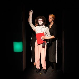 Kate, a female human sized puppet with red 80s glasses and a tight perm, is standing with one arm up in the air, fingers bent over an invisible handle. She is holding a red a4 binder folder and a black dictaphone. Behind her are 2 puppeteers who are holding each hand and looking at Kate. Kate wears pink trousers and a white, speckled shirt.