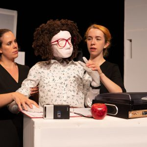 Kate is sitting behind a white desk looking to the side. She has one hand up as though thinking and one hand on the desk. She is a female human sized puppet with red 80s glasses and a tight perm, and there are puppeteers on either side of her, one on each hand. They are female puppeteers wearing black, with their hair tied back, one has ginger hair whilst the other has dark hair. On the desk is a record player, a red apple and a black and silver dictaphone, as well as some paperwork underneath Kate's right hand.