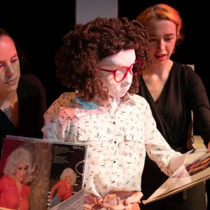 Kate, a female human sized puppet with red 80s glasses and a tight perm, is standing in a record shop looking through records. There is a box of vinyl on a desk, one record is visible showing Dolly Parton in a red shirt with very big 80s hair. There are also two puppeteers partially visible in the image, they are each holding one of Kate's hands.