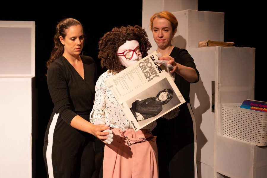 Kate and 2 puppeteers stand looking at a Bobby Crush record cover. Kate, a female human sized puppet with red 80s glasses and a tight perm, is holding up the record, partially covering her face. The puppeteers are female, wearing black with their hair tied back, one has ginger hair whilst the other has dark hair. In the background is a box of records on a white set block with step like levels on one side.