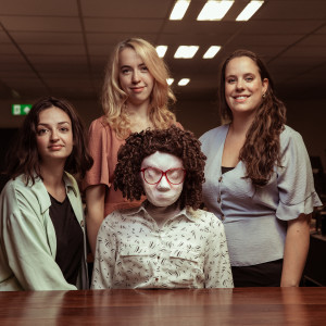 Kate and her puppeteers are behind a dark brown desk, Kate is sitting whilst the others are standing. Kate is a full sized puppet with big 80s glasses and brown hair in a tight perm. Anne has shoulder length brown hair and brown eyes, Hattie has long blonde hair and a peach coloured top, Molly has long brown hair and a bright smile.