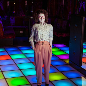 Kate stands with her hands in her pockets, she is wearing high waisted pastel pink trousers and a patterned black and white shirt. Kate is in a club, with a mutli-coloured light up floor and mirror balls hanging from the ceiling. Kate is a full sized puppet with big red glasses and a tight perm.