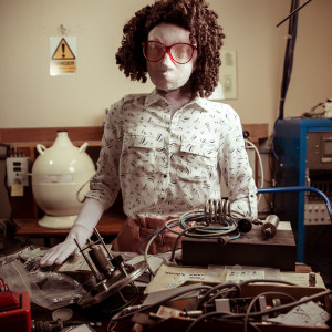 Kate, a female human sized puppet with a big red glasses and a tight perm, stands behind a mess of physics equipment on a desk. There is a yellow danger sign on the wall behind her.