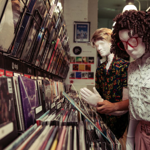 A close up of Kate and Alan in a record shop, there are shelves of vinyl on the left and a blurred Beatles poster in the background. Kate, a female human sized puppet with red 80s glasses and a tight perm, is looking at an 80s record. Standing next to her is Alan, a full sized male puppet with an 80s wham style haircut, Alan is wearing a vibrant patterned shirt.