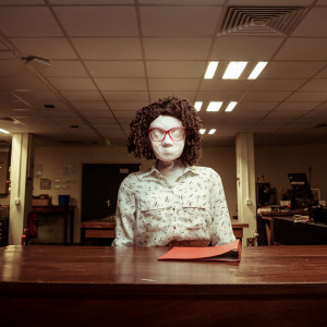 Kate, a female human sized puppet with red 80s glasses and a tight perm, sits behind a dark brown wooden desk in a badly lit office space. In the background there are some computers and equipment on other desks. Kate has a red folder in front of her and is looking directly at the camera.