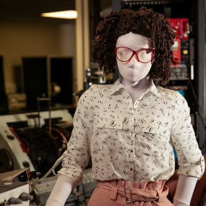 Kate, a female human sized puppet with big, red, 80s glasses and a tight perm, stands behind behind a desk with one hand resting on her red folder, and one hand in her pocket. There is an oscilloscope partially in view on the desk, with lots of physics equipment in the background.