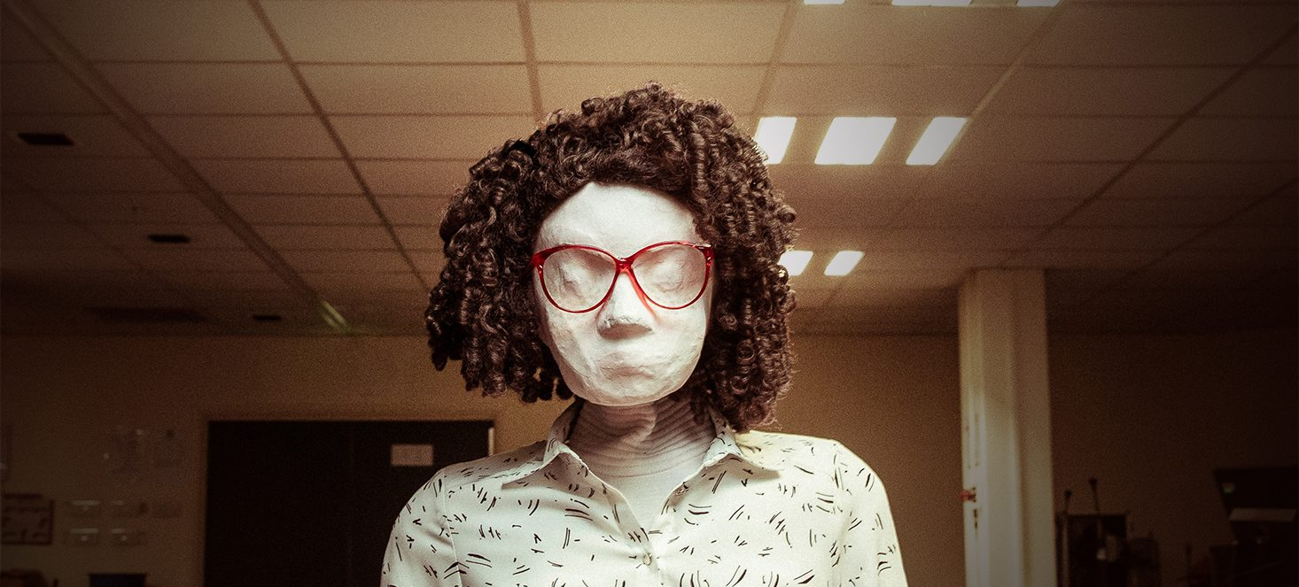 Kate, a female human sized puppet with red 80s glasses and a tight perm, sits behind a dark brown wooden desk in a badly lit office space. In the background there are some computers and equipment on other desks. Kate is looking directly at the camera.