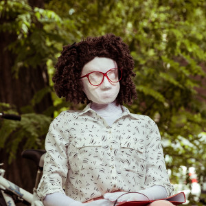 Kate, a female human sized puppet with a big red glasses and a tight perm, has headphones and a folder. She is in a park with grass and a big tree and bike in the background.