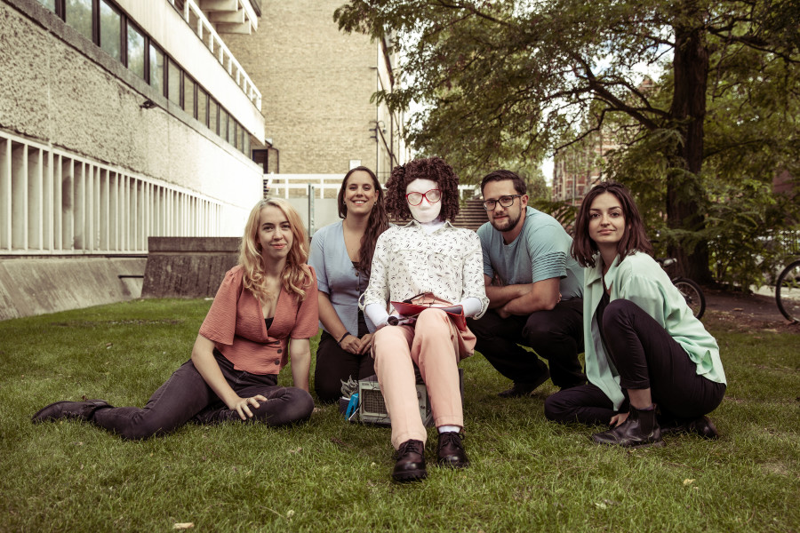The full cast of Flux sits on the grass outside a grey, concrete building. On the far left is Hattie, with blonde hair and peach top, then Molly with long brown hair and a pastel blue top, full sized puppet Kate sits in the middle, with big 80s glasses and a tight perm. Next to Kate is Matt with short brown hair and a light blue top and he is next to Anne with shoulder length brown hair and a light green shirt.
