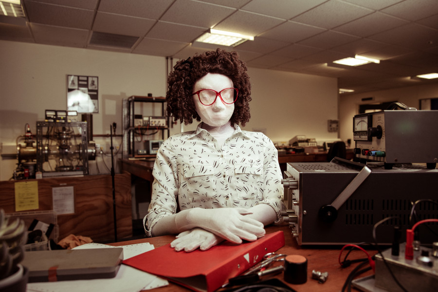 Kate, a female human sized puppet with a big 80s glasses and a tight perm, sits in a science lab with an oscilloscope, her hands are folded over her red folder on the dark wooden desk.