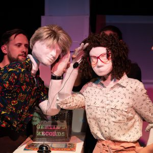 Kate, a female human sized puppet with red 80s glasses and a tight perm, is standing next to Alan, a full sized male puppet with an 80s wham style haircut. They are in a record shop represented by a box of vinyl on a desk with a sign saying Gertie's Records. There is also a record on display and a silver shop bell. Kate and Alan are holding wire frame headphones, one side in each hand and leaning into listen to the same record. Also visible are three puppeteers, 2 holding Kate and 1 holding Alan.